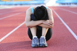Athlete sitting on track holding her knees with her head down in disappointment